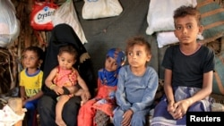 Malnourished boy Hassan Merzam Muhammad sits with his mother and brothers and sisters inside their hut in Abs district of Hajjah province, Yemen November 20, 2020. (REUTERS/Eissa Alragehi)