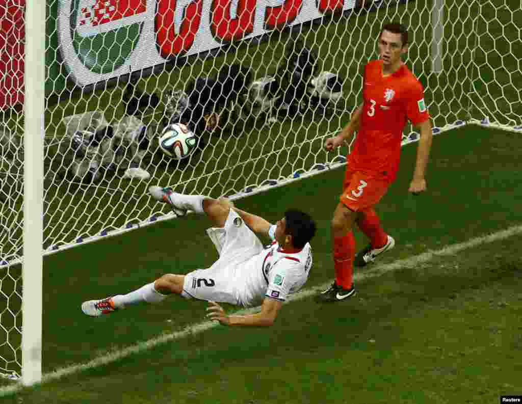 Costa Rica's Johnny Acosta clears the ball from the goalpost during extra time against Netherlands at the Fonte Nova arena in Salvador, July 5, 2014.