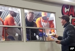 Former California Gov. Arnold Schwarzenegger serves breakfast to firefighters, Nov. 21, 2018, in Chico, Calif. Schwarzenegger has made a surprise visit to firefighters battling a deadly blaze in Northern California, helping serve them breakfast while providing encouragement.