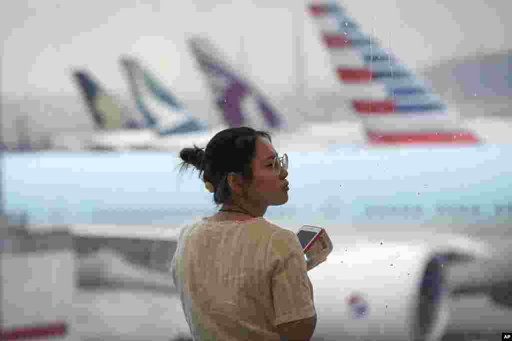 نگاه یک مسافر به خط هواپیماهای پارک شده در فرودگاه بین المللی هنگ کنگ. معترضان در این شهر، برای اعتراض به دخالت های چین، فرودگاه بین المللی هنگ کنگ را تعطیل کردند.