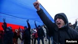 Manifestantes marchan bajo una bandera rusa en la ciudad de Simferopol, en Crimea.