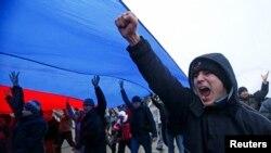 Kırım'ın başkenti Simferol'da dev bir Rus bayrağı ile yürüyen Moskova yanlısı göstericiler