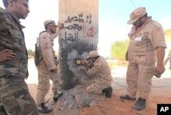 Des combattants du CNT en train de détruire la Porte orientale de Syrte qui séparait la ville natale de Kadhafi des villages de la région