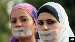 "Jordanian journalists protest in front the Jordanian House of Parliament, with their mouths covered with tape and the words ""article 23,"" in Arabic, against proposed changes to the anti-corruption law they believe will muzzle press freedoms, Amman, Septem"
