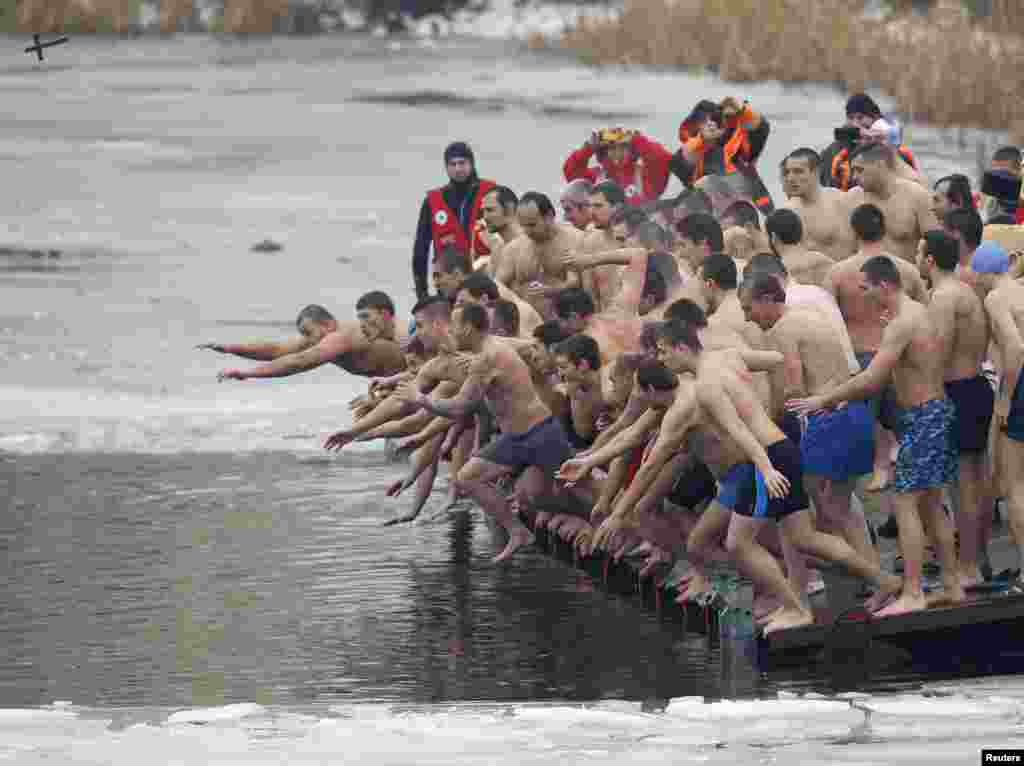 Men jump into the waters of a lake in an attempt to grab a wooden cross on Epiphany Day in Sofia, Bulgaria.