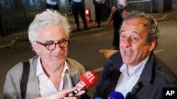Michel Platini, phải, và luật sư của ông, William Bourdon, trả lời các phóng viên sau khi cựu doanh thủ Pháp được thả bên ngoài văn phòng cảnh sát chống tham nhũng và tội phạm tài chính ở Nanterre, ngoại ô Paris, hôm 19/6.