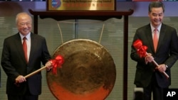 Hong Kong Exchanges Chairman Chow Chung-kong, left, and Hong Kong Chief Executive Leung Chun-ying pose before beating a gong during the launch ceremony of the Shanghai-Hong Kong Stock Connect in Hong Kong Monday, Nov. 17, 2014. (AP Photo/Vincent Yu)