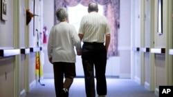 FILE - An elderly couple walks down a hall in Easton, Pennsylvania, Nov. 6, 2015.