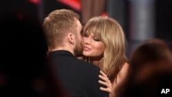 Taylor Swift (kanan) memeluk Calvin Harris setelah memenangkan penghargaan di ajang Billboard Music Awards, di Las Vegas bulan Mei lalu.