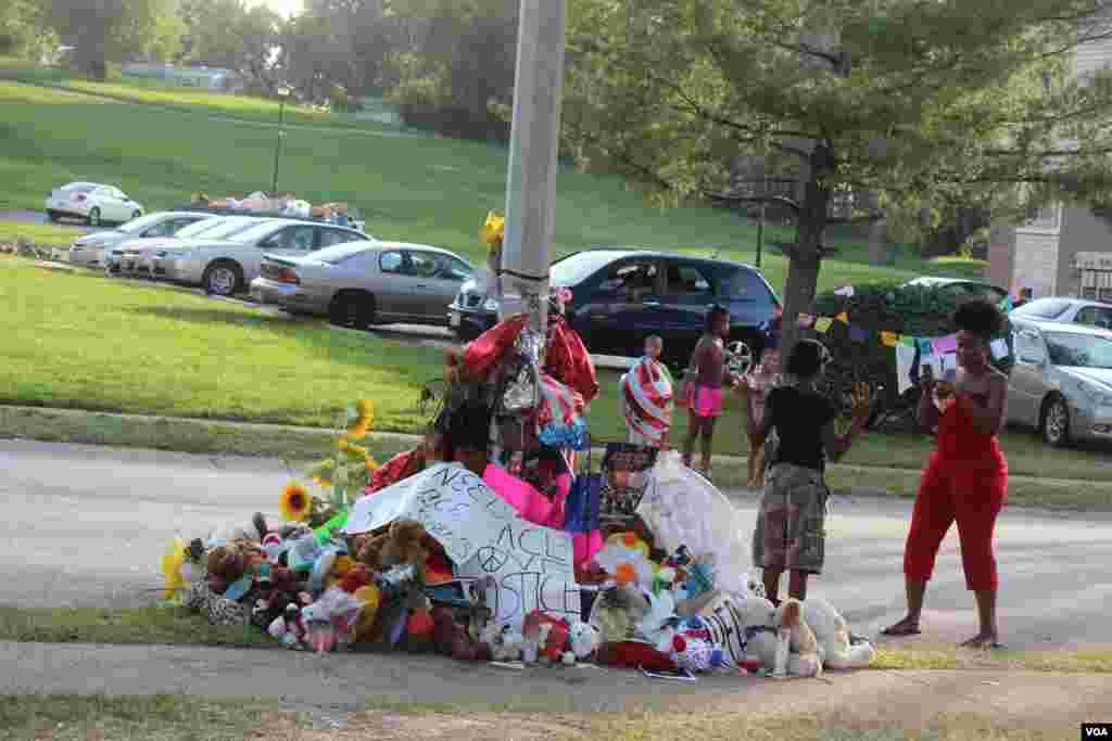 Cientos de personas se acercan al sitio en donde Michael Brown murió en manos de agente Darren Wilson, para rendir una especie de homenaje al joven afroestadounidense. [Foto: Gesell Tobias, VOA]