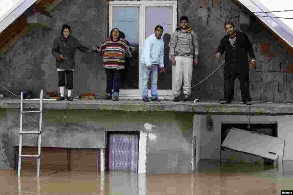 People stand on a terrace of their flooded house as they wait to be evacuated in the town of Obrenovac, east of Belgrade, Serbia.