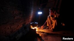 A woman cooks over a wood-burning fire under a battery-run emergency light during a power outage in a slum in Islamabad, Pakistan, Apr. 29, 2013.