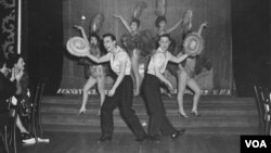"Jimmy ""Jay"" Borges, left, and Tony Wing in performance at Forbidden City; Wing's sister, Arlene, is seen above his head; Sisko Borges, Jimmy Jay's then-wife, is behind Jay, to the right, 1959 (Courtesy DeepFocus Productions, Inc.)."