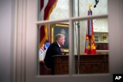 FILE - As seen from a window outside the Oval Office, President Donald Trump gives a prime-time address about border security, at the White House in Washington, Jan. 8, 2018.