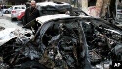 Một chiếc xe bị hư hại hoàn toàn sau vụ nổ bom trong quận Bab Touma
