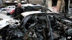Seorang pria Suriah menatap mobil yang hancur yang bom mobil di daerah Bab Touma, Minggu (21/10).