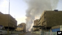 Smoke rises from the site of bomb attacks targeted Baghdad's wholesale Shurja market, Iraq, November 6, 2011.