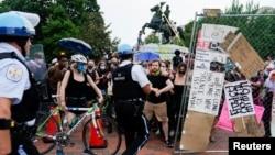 Petugas Polisi Taman AS bentrok dengan para pengunjuk rasa yang melindungi demonstran lain yang mencoba merobohkan patung Presiden AS Andrew Jackson di tengah-tengah Taman Lafayette di depan Gedung Putih, Washington, DC, 22 Juni 2020.