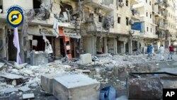 ຮູບນີ້ ຊຶ່ງນຳອອກເຜີຍແຜ່ໂດຍ ໜ່ວຍປົກປ້ອງພົນລະເຮືອນ ໝວກເຫລັກຂາວ ສະແດງໃຫ້ເຫັນວ່າ ພວກຜູ້ຊາຍ ຢືນຢູ່ຕາມຊາກຫັກພັງ ຫຼັງຈາກການໂຈມຕີທາງອາກາດ ຕໍ່ພາກຕາເວັນອອກ ຂອງເມືອງ Aleppo ເມື່ອວັນທີ 9 ກັນຍາ ຜ່ານມາ