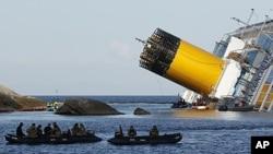 ພວກນັກດໍານໍ້າ ນັ່ງຢູ່ທາງຂ້າງກໍາປັ່ນທ່ອງທ່ຽວ Costa Concordia ທີ່ຄາໂຫງ່ນຫິນນອກຝັ່ງທະເລເກາະ Giglio ຂອງອີຕາລີ., ວັນທີ 24 ມັງກອນ 2012.