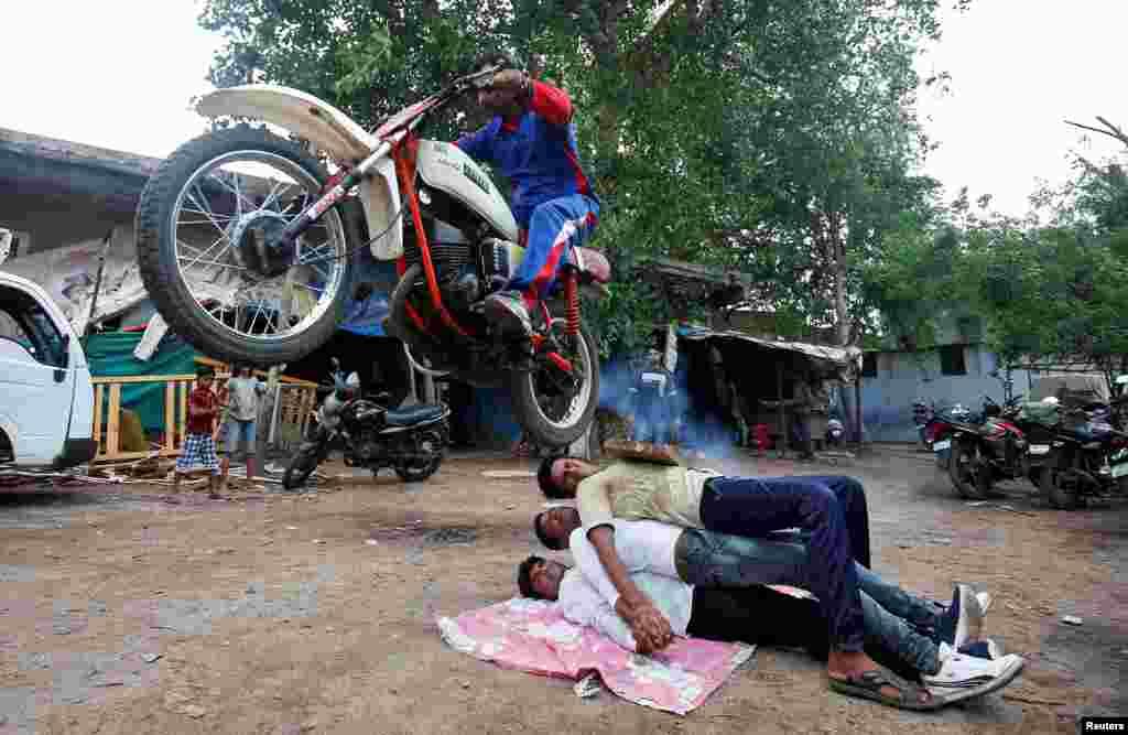 សាសនិកជនហិណ្ឌូសម្តែងសៀកជាមួយនឹងម៉ូតូរបស់គាត់មុននឹងពិធីបុណ្យប្រចាំឆ្នាំ Rath Yatra ក្នុងទីក្រុង Ahmedabad ប្រទេសឥណ្ឌាកាលពីថ្ងៃទី០៣ កក្កដា ឆ្នាំ ២០១៨។