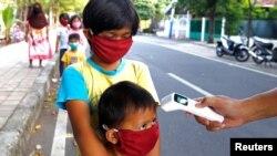 Trẻ em được kiểm tra thân nhiệt trước khi nhận thực phẩm miễn phí tại Jakarta, Indonesia, ngày 14/5/2020.