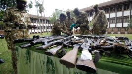 FILE - Kenya Wildlife Service officials inspect illegally held firearms recovered from poachers, at their headquarters in Kenya's capital Nairobi, June 22, 2012.