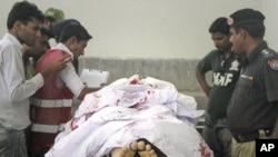 پـۆلیس و چهند کارمهندێـکی تهندروستی له نهخۆشـخانهیهکی شـاری کهراچی سهیری تهرمی دیپـلۆماتهکهی سعودیه حهسهن ئهلقحطانی دهکهن، دووشهممه 16 ی پـێـنجی 2011