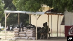 Nigerian troops man a checkpoint to prevent sectarian violence.