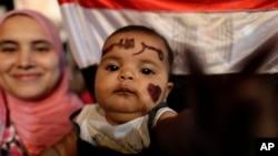 Một em bé sáu tháng tuổi với chữ Morsi bằng tiếng Ả rập viết trên trán