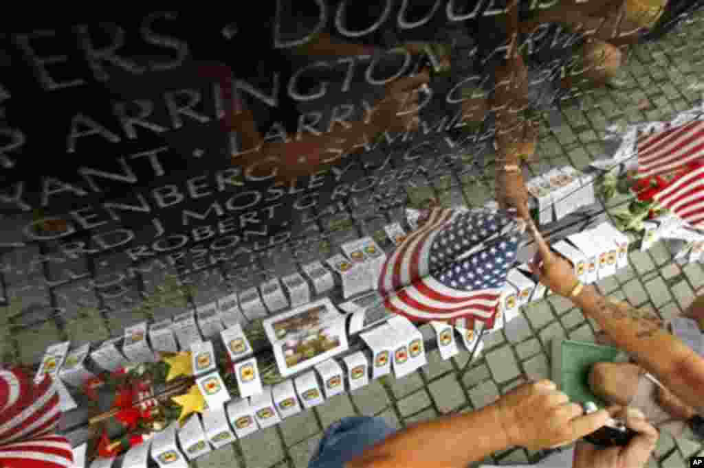 Visitors find a name on at the wall of the Vietnam Veterans Memorial in Washington on Sunday, May 29, 2011. Motorcyclists are in Washington for the traditional annual Rolling Thunder events during the Memorial Day weekend. (AP Photo/Jose Luis Magana)