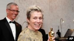 奥斯卡最佳女主角奖得主弗朗西斯·麦克道曼拿着她荣获的金像参加在奥斯卡典礼之后的好莱坞舞会(2018年3月4日)