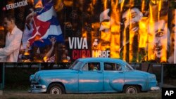 """A taxi driving a classic American car passes a billboard that reads in Spanish: """"Long live free Cuba"""" in Havana, Cuba, Monday, March 14, 2016. U.S. President Barack Obama will travel to Cuba on March 20. (AP Photo/Desmond Boylan)"""