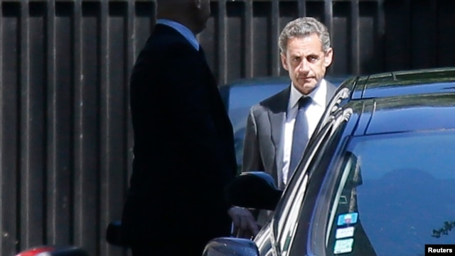 Former French President Nicolas Sarkozy leaves his residence in Paris, July 2, 2014.