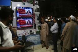 FILE - People listen a televised speech of Pakistani Prime Minister Imran Khan regarding his visit to Saudi Arabia, in Karachi, Pakistan, Oct. 24, 2018.
