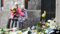 Children lay flowers outside of Windsor Castle in Windsor, England after the announcement regarding the death of Britain's Prince Philip, Friday, April 9, 2021.