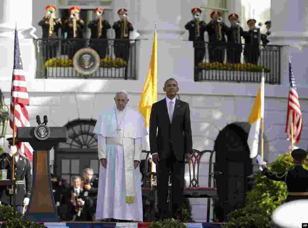 Presiden AS Barack Obama dan Paus Fransiskus dalam sikap sempurna saat lagu kebangsaan kedua negara dikumandangkan di lapangan rumput selatan Gedung Putih di Washington (23/9). (AP/Pablo Martinez Monsivais)