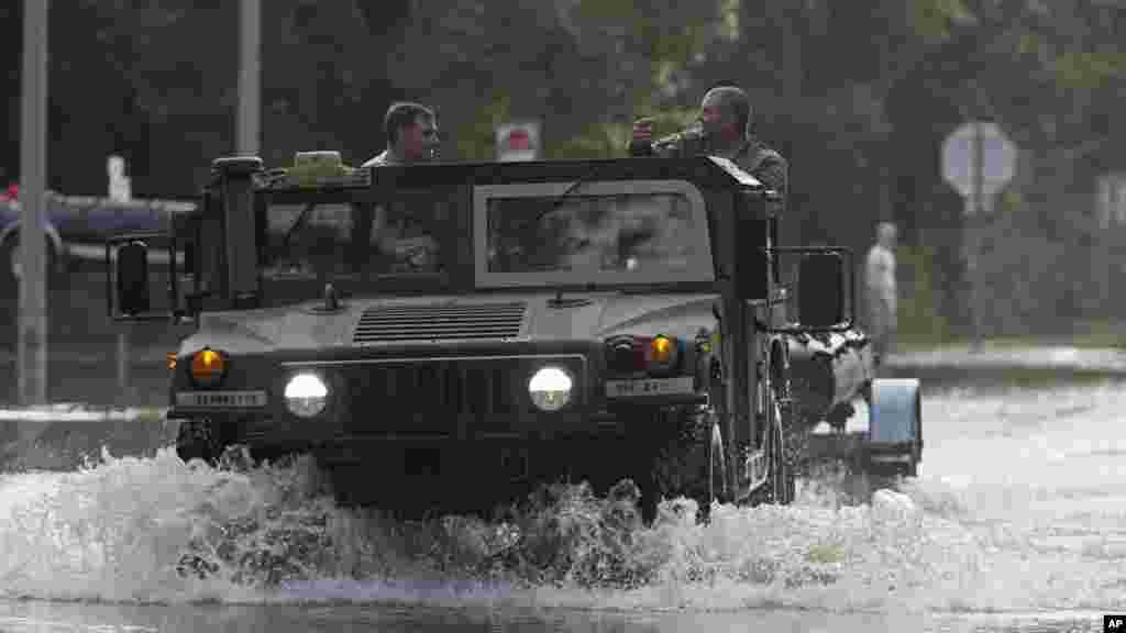 Une voiture de la Garde nationale traverse l'eau, le 14 août 2016.