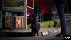 """Un enfant perdu est assis sur un trottoir après l'éruption du volcan Nyiragongo, au poste frontière connu sous le nom de """"Petite Barrière"""" à Gisenyi, au Rwanda, le 23 mai 2021."""