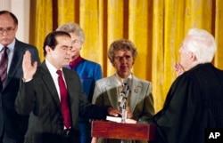 ຫົວໜ້າຕຸລາການ ທີ່ກຳລັງຈະກະສຽນ ທ່ານ Warren Burger (ຂວາ) ທຳພິທີ ສາບານຕົວ ໃຫ້ແກ່ທ່ານ Antonin Scalia, ໃນຂະນະທີ່ພັນລະຍາ ຂອງທ່ານ Scalia ທ່ານນາງ Maureen ຖືຄຳພີ Bible ຢູ່ໃນຫ້ອງຕາເວັນອອກ ຂອງທຳນຽບຂາວ, ວັນທີ 26 ກັນຍາ 1986.