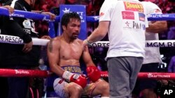 FILE - Trainer Freddie Roach speaks to Manny Pacquiao between rounds against Yordenis Ugas, of Cuba, in a welterweight championship boxing match in Las Vegas, Aug. 21, 2021. Pacquiao is officially hanging up his gloves. FILE - Trainer Freddie Roach speaks