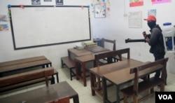 Petugas menyemprotkan cairan desinfektan di ruang kelas di sebuah sekolah di Surabaya (foto VOA/Petrus Riski).