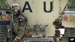 Soldado ugandês da força da União Africana na Somália (AMISOM) fotografado junto a um blindado