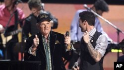 Mike Love of the band Beach Boys and Adam Levine, right, of the band Maroon 5 speak onstage after performing during the 54th annual Grammy Awards in Los Angeles, February 12, 2012. (AP Photo/Matt Sayles)