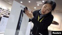 Seorang pegawai toko di Wuhan, provinsi Hubei, Tiongkok, membersihkan papan iklan iPhone 5. (Foto: Reuters)