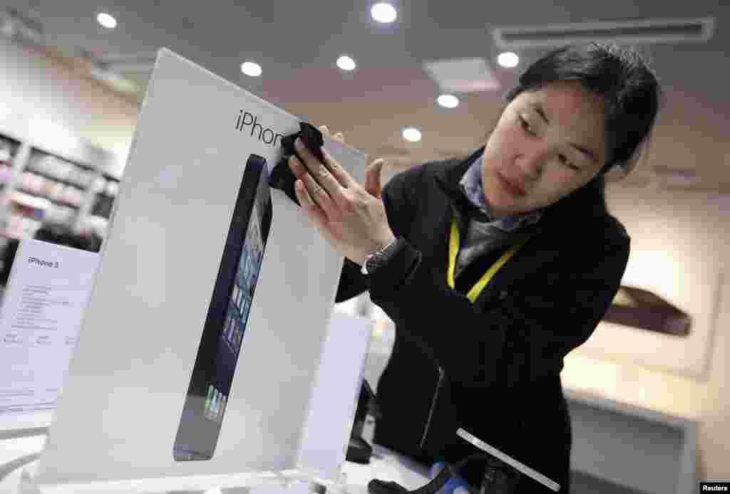 在武汉,一名商店雇员擦拭苹果手机的广告牌。中国是继美国和欧洲之后苹果公司的第三大市场。公司2017财年约20%的收入来自中国。中国还拥有大规模的苹果生产基地,尽管iPhone面临中国本土的强劲竞争对手。