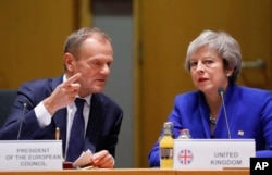 FILE - British Prime Minister Theresa May and European Council President Donald Tusk attend a round table meeting at an EU summit in Brussels, Nov. 25, 2018.