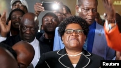 Zimbabwe's former vice president Joice Mujuru (c) smiles while addressing supporters in Harare, March 1, 2016.