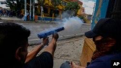 Manifestantes anti governamentais disparam contra a policia com arma de fogo de fabrico caseiro
