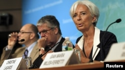 IMF Managing Director Christine Lagarde (R) speaks at a conference after the release of IMF's annual report on the U.S. economy in Washington, July 3, 2012.